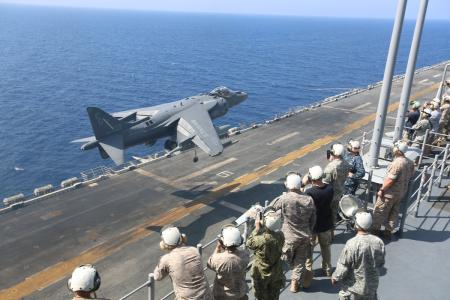 Combined Joint Task Force - Horn of Africa staff members watch an AV-8B Harrier jet with Marine Medium Tiltrotor Squadron (VMM) 263 (Reinforced), 22nd Marine Expeditionary Unit (MEU), land aboard the USS Bataan (LHD 5). The 22nd MEU is deployed with the Bataan Amphibious Ready Group as a theater reserve and crisis response force throughout U.S. Central Command and the U.S. 5th Fleet area of responsibility. (U.S. Marine Corps photo by Cpl. Caleb McDonald/Released)